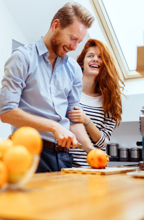 happy couple cooking in kitchen with peace of mind from security and alarm system