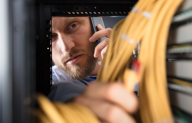 security technician checking alarm panel with bundles of wire