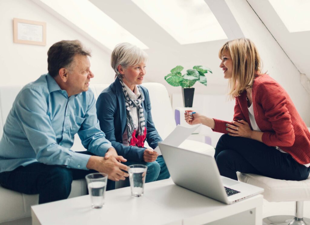 saleswoman talking with couple in home